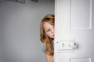 girl peeking head around door